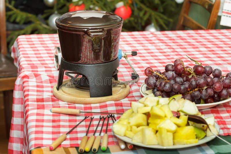 Parti för fondue för söt choklad för efterrätt med skivor av äpplen, päron, ananors och druvor arkivfoton