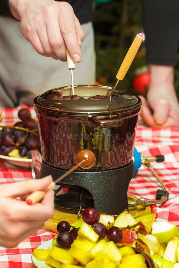 Parti för fondue för söt choklad för efterrätt med stycken av äpplen, päron, ananors och druvor royaltyfri bild