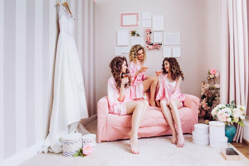 Parti f?r flickor Flickv?nner dricker rosa champagne f?r den gifta sig ceremonin i rosa pyjamas royaltyfria bilder