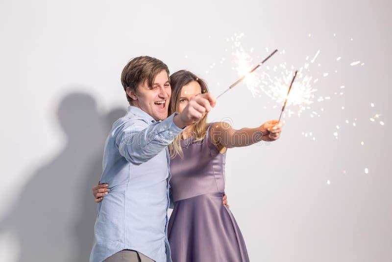 Parti, gyckel och feriebegrepp - ungt lyckligt par med tomtebloss på vit bakgrund arkivfoton