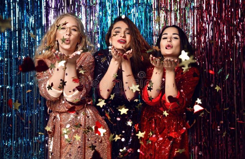 Parti- och feriebegrepp Tre glamourkvinnor i lyx bl?nker paljetter kl?r ha gyckel arkivfoto