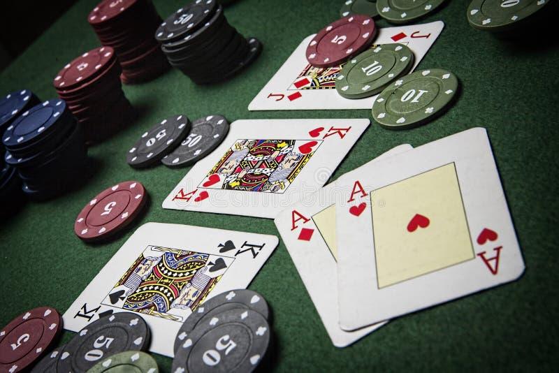 Partia pokeru ciekawi z ewentualną wygraną kombinacją na zielonym tle zdjęcia royalty free