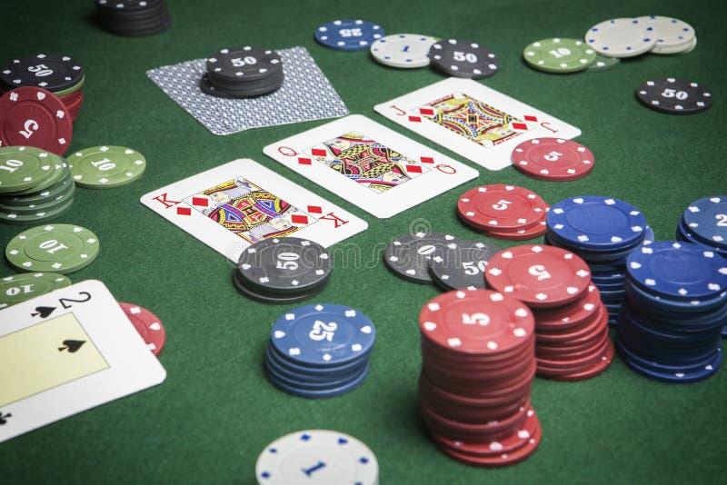 Partia pokeru ciekawi z ewentualną wygraną kombinacją na zielonym tle zdjęcie royalty free
