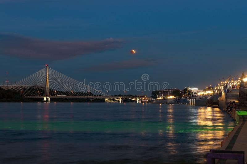 Partial eclipse moon over Warsaw city i stock photography