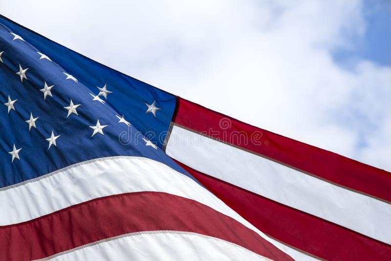 American Flag with Blue Sky and Clouded Background. Partial, View of American Flag with Blue Sky and Clouded Background royalty free stock image