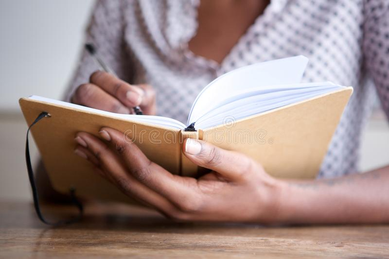 Partial portrait of black female author at home writing in journal. Close up partial portrait of black female author at home writing in journal royalty free stock images