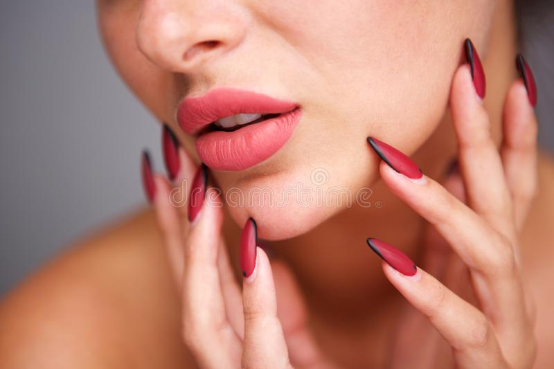 Partial portrait of woman with red manicure and flawless complexion. Close up partial portrait of woman with red manicure and flawless complexion royalty free stock photography