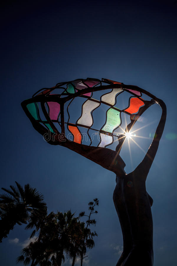Partial solar eclipse shines through the colorful metal statue royalty free stock photos