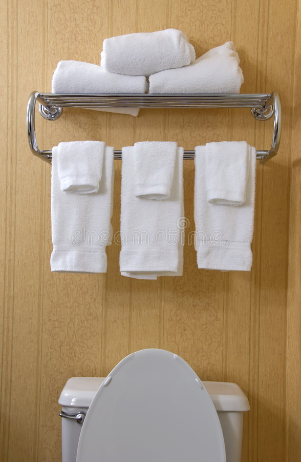 Partial toilet and towel rack. Top of toilet and towel rack with white terry cloth towels royalty free stock photos