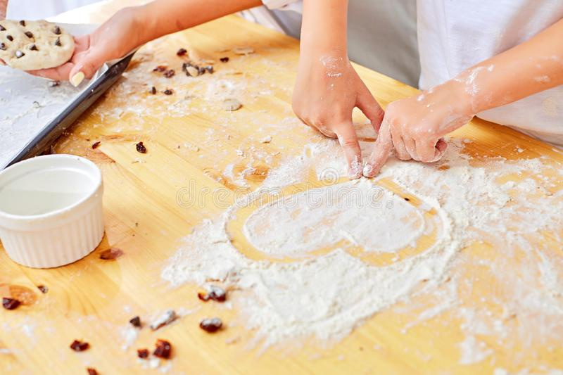 Girl draws a heart on the board with flour stock photo