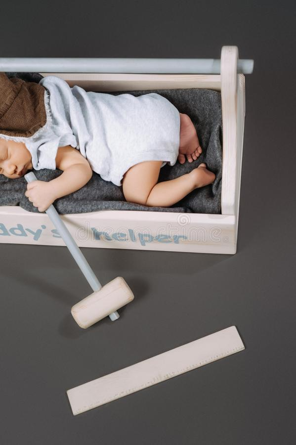 Partial view of adorable baby with hammer in hand sleeping in wooden toolbox with daddys. Helper lettering stock image