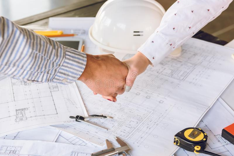 Architects shaking hands. Partial view of architects shaking hands with blueprints and architect equipment on table stock image