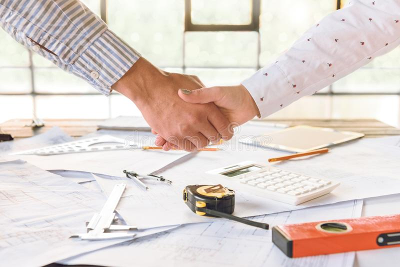 Architects shaking hands. Partial view of architects shaking hands with blueprints and architect equipment on table stock images