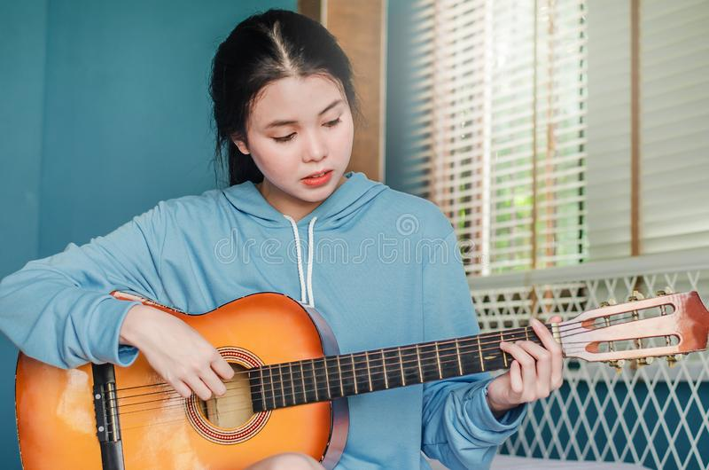 Partial view of asian girl  playing on acoustic guitar from the morning wake up in bedroom at home stock images