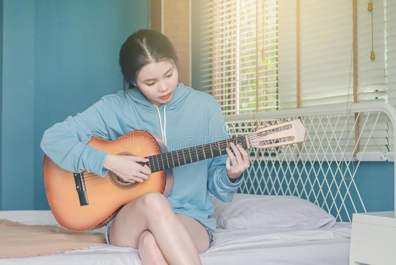 Partial view of asian girl  playing on acoustic guitar from the morning wake up in bedroom at home royalty free stock image
