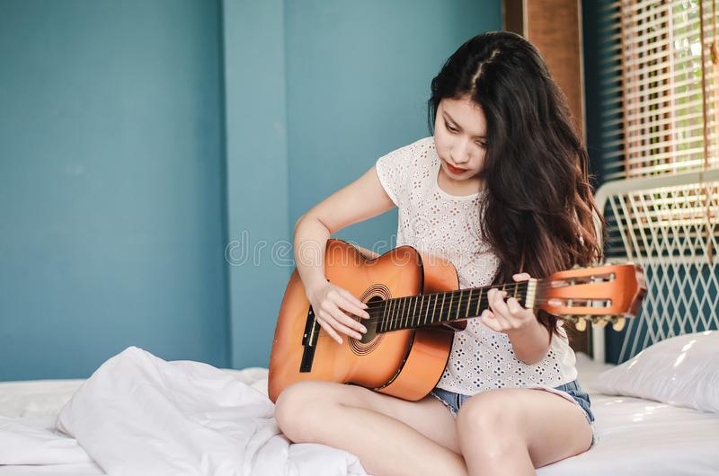 Partial view of asian girl  playing on acoustic guitar from the morning wake up in bedroom at home stock photography