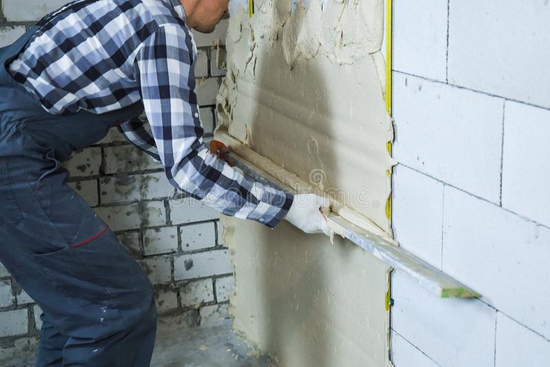 Partial view of builder plastering on block wall. Worker in uniform doing interior renovation. house, building and construction stock photos