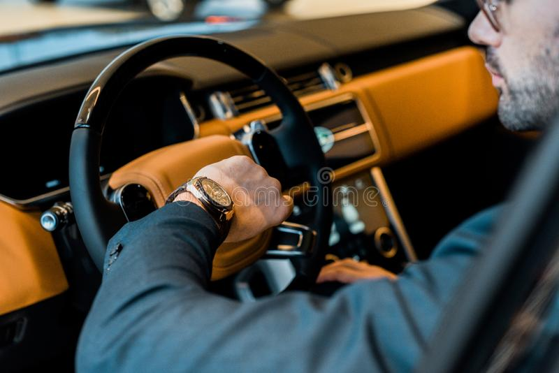 Partial view of businessman checking watch. In luxury car stock image