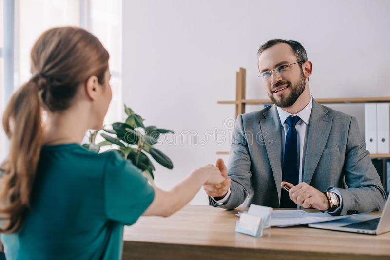 partial view of businessman and client shaking hands during meeting stock photography