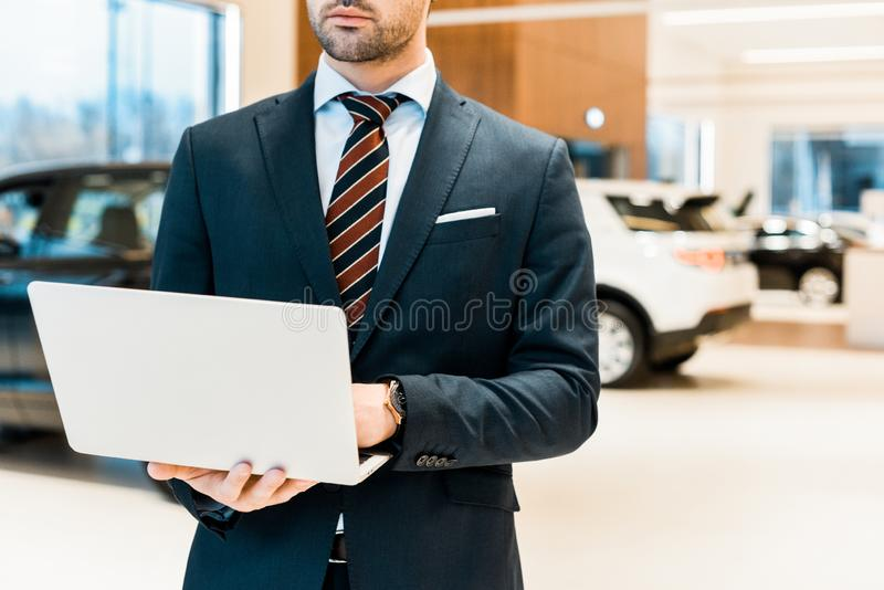 Partial view of businessman in formal suit using laptop. At dealership salon royalty free stock images