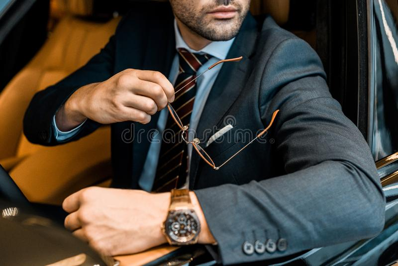 Partial view of businessman with luxury watch holding eyeglasses while sitting. In car stock photography