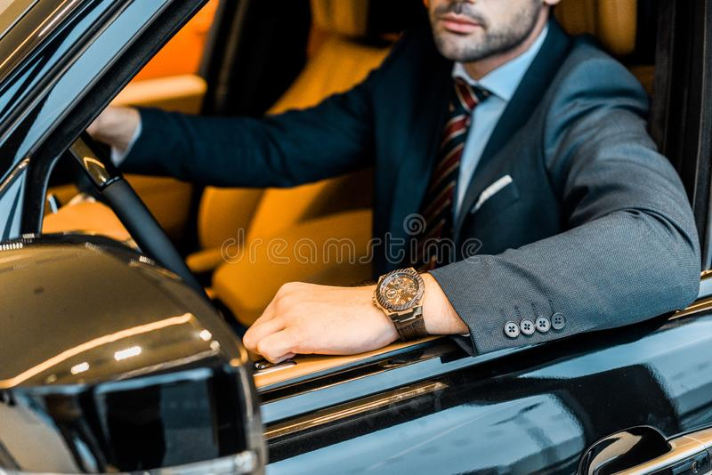 Partial view of businessman with luxury watch sitting. In automobile stock photography
