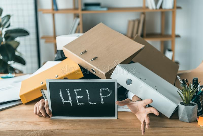 Partial view of businessman lying under pile of folders with help blackboard in hands while missing deadlines. At work royalty free stock photos