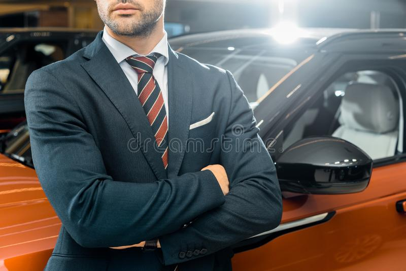 Partial view of businessman posing. With crossed arms near automobile royalty free stock photo