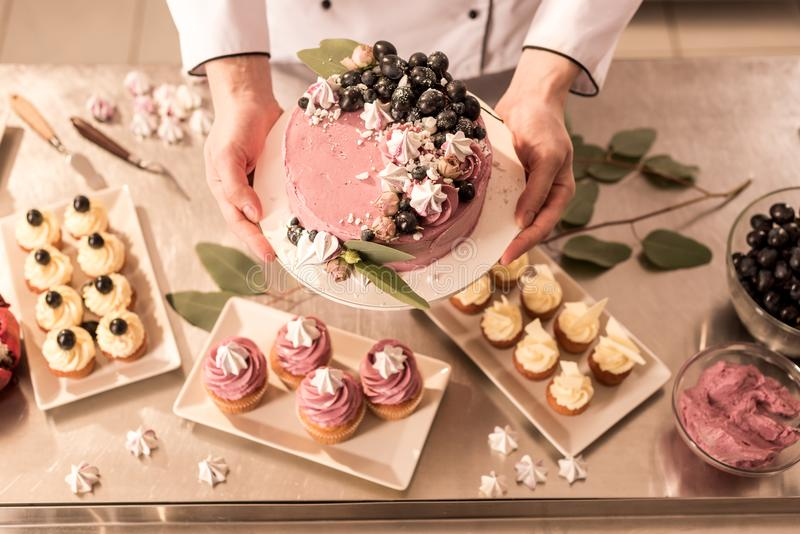 Partial view of confectioner holding cake in hands. In restaurant kitchen stock photo