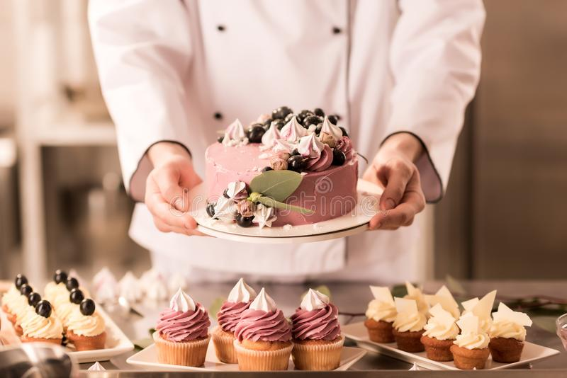 Partial view of confectioner holding cake in hands. In restaurant kitchen stock photography