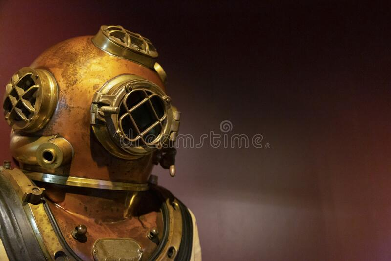 A partial view of a copper and brass antique diver`s helmet and suit against a plain dark red background royalty free stock photo