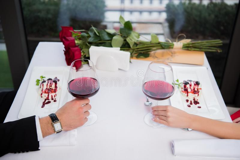 Partial view of couple with glasses of red wine sitting at table on st valentine day. In restaurant stock photography