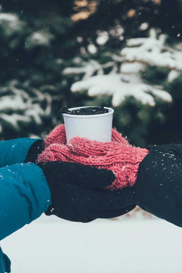 partial view of couple holding thermocup with hot drink together in winter forest stock images