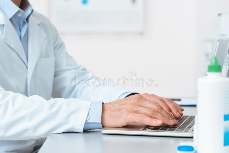 Partial view of doctor in white coat working on laptop at workplace. In clinic royalty free stock images