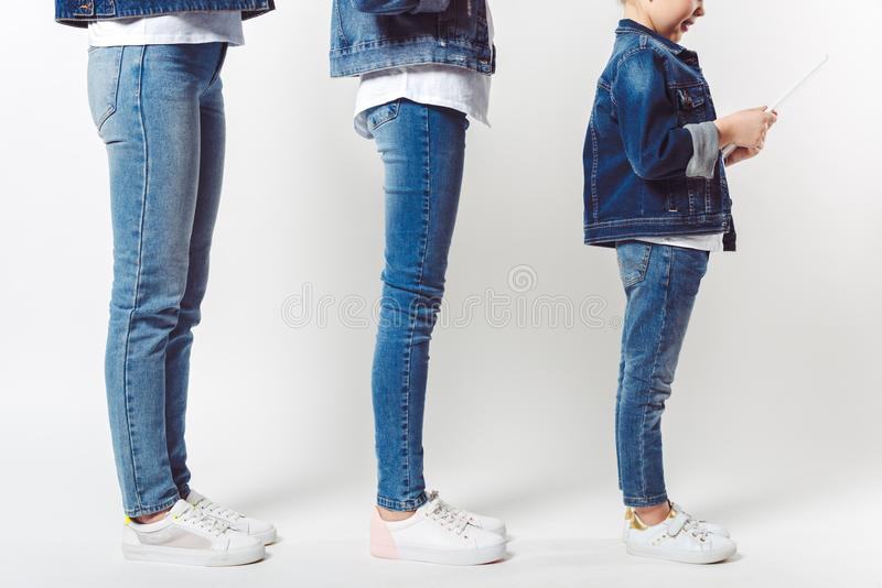 Partial view of family and kid with tablet in similar denim clothing standing in row. Isolated on grey stock photography