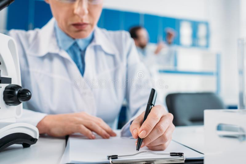 Partial view of female scientist making notes in notepad at workplace with colleague behind. In lab stock photo