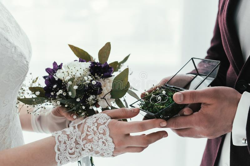 partial view of groom with wedding rings and bride with wedding bouquet royalty free stock image