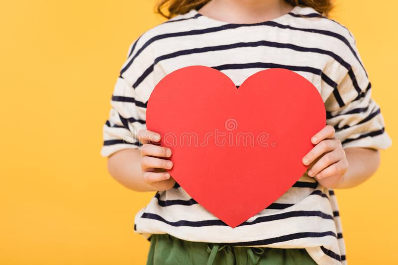 Partial view of kid with red paper heart in hands. Isolated on yellow, st valentines day concept royalty free stock image
