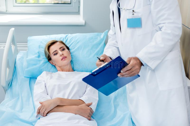 Partial view of male doctor with stethoscope over neck pointing at clipboard to female patient in hospital. Room royalty free stock photos
