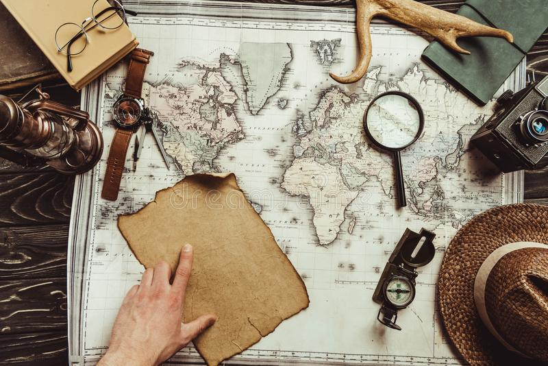 partial view of male hand, map, blank burnt paper, watch, magnifying glass, compass and hat stock image