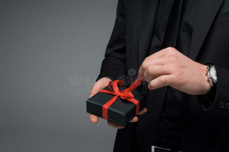 Partial view of male hand untying ribbon on gift box isolated on grey, international womens day concept stock photography