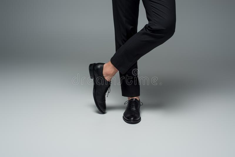 Partial view of male legs in black formal shoes on grey royalty free stock images