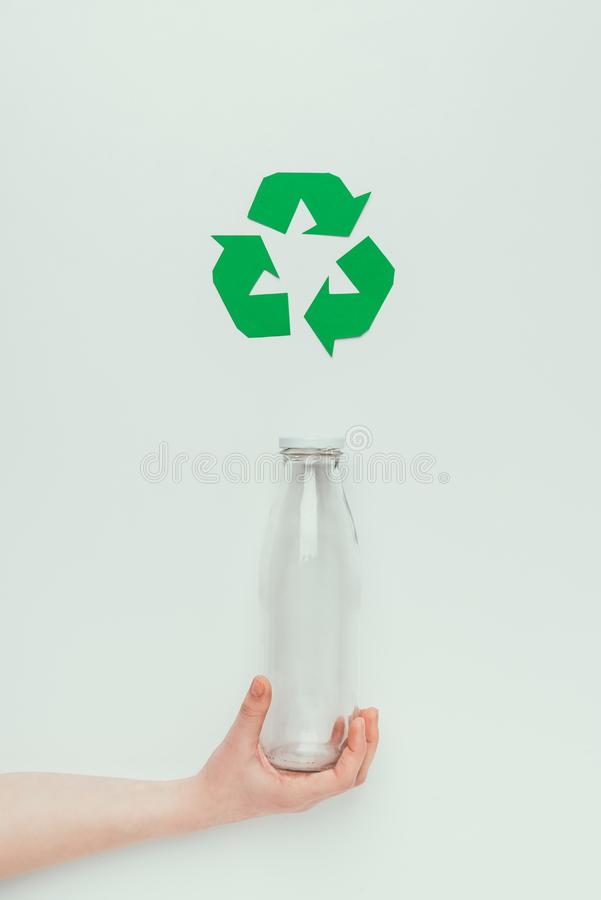 Partial view of man holding glass bottle with recycle sign. On grey royalty free stock photo