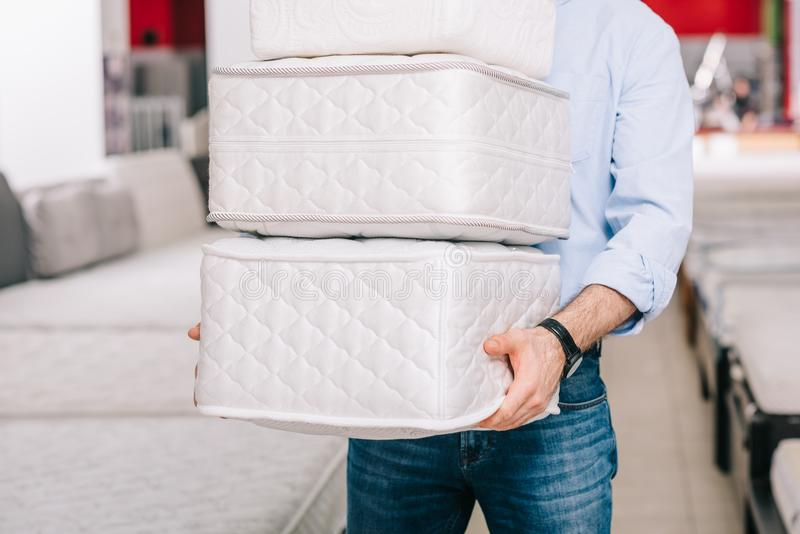 Partial view of man holding pile of folding mattresses in hands in furniture store royalty free stock image