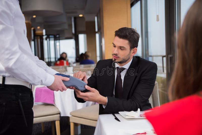 Partial view of man paying for order with credit card. In restaurant stock images