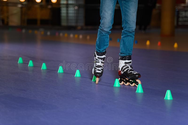 Partial view of man in roller skates skating on roller rink. With cones stock images