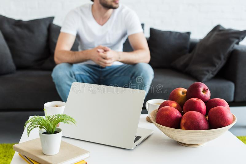 partial view of man sitting on couch near table with coffee cups, laptop, books and apples at home royalty free stock photos