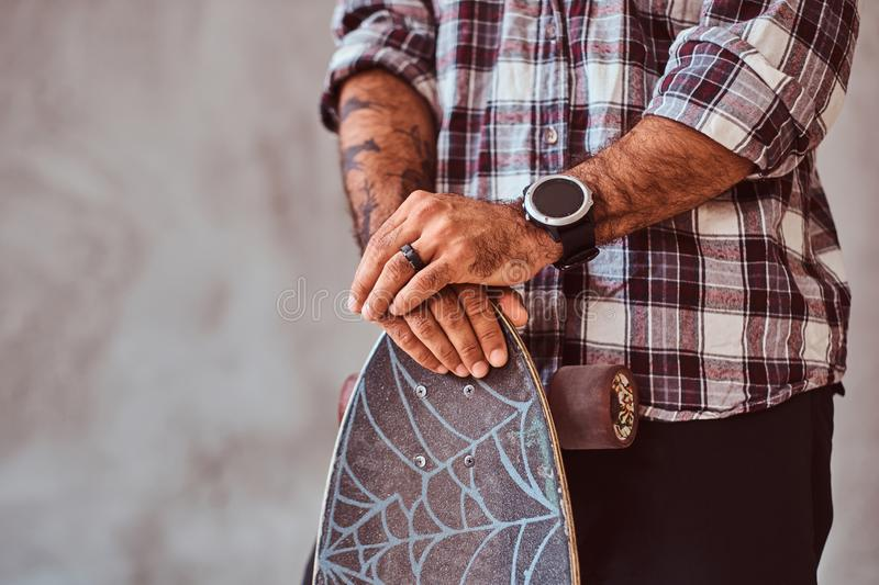 Partial view of a man wearing a checkered shirt leaning on a skateboard. Isolated on a gray background. Partial view of a man wearing a checkered shirt leaning royalty free stock images