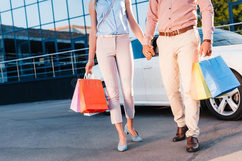 Partial view of married couple with shopping bags holding hands while walking. On street royalty free stock photography
