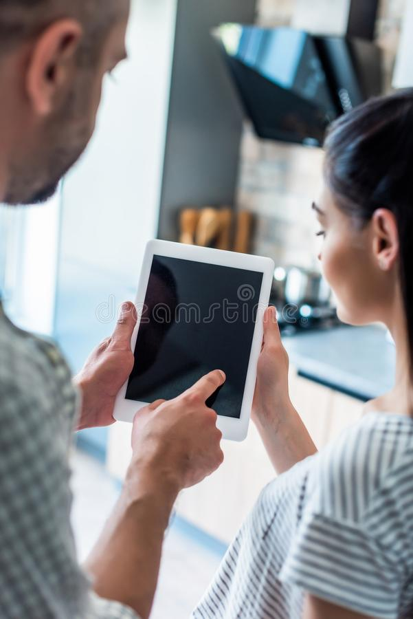 Partial view of married couple using digital tablet with blank screen together at home smart. Home concept stock image